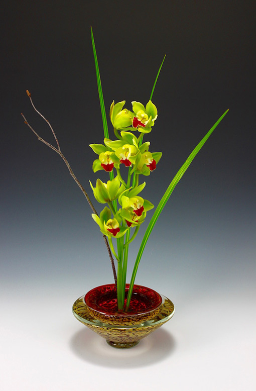 Ruby glass ikebana flower bowl with orchid floral arrangement