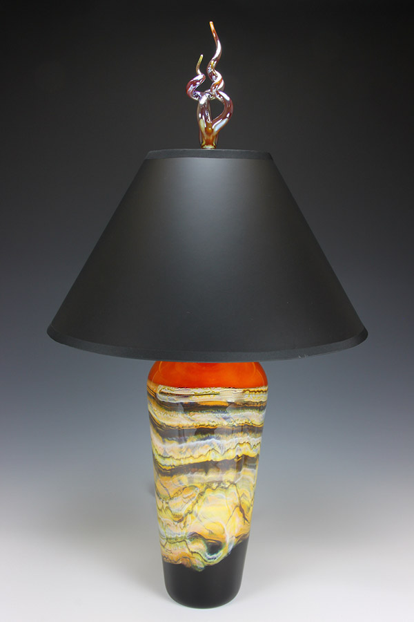 Art glass lamp with gold foil lined black lampshade and gold flame finial