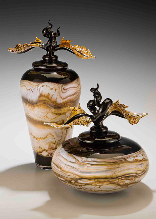 Pair of black glass vessels with lids and sculpted glass finials